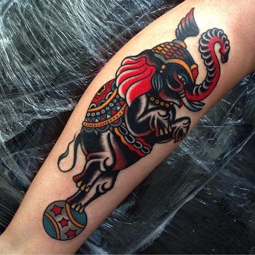 Um preto e vermelho elefante é ilustrado no estilo tradicional como ele fica no topo de uma bola.