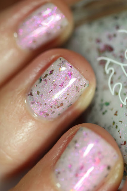 white crelly with magenta shimmer swatched on white person's nails