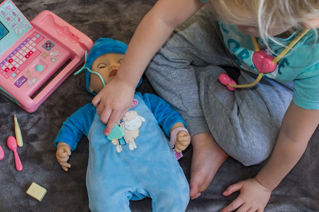 Another view of a child scanning the blue toy doll Baby Alexander with the Pink Baby Annabell medical scanner for the review