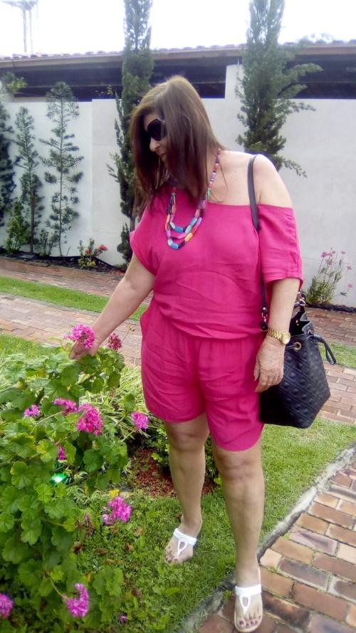 #PraCegoVer: Mulher sorrindo, cheirando flor.