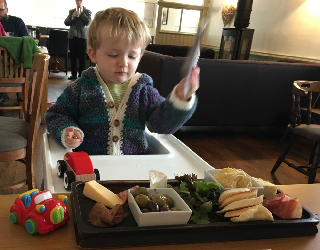 toddler-in-high-chair-in-restaurant-with-platter-of-food