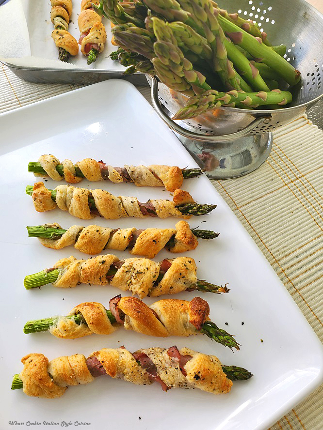this is a white tray full of spiral wrapped asparagus appetizers and more of this vegetable in a colander in the background