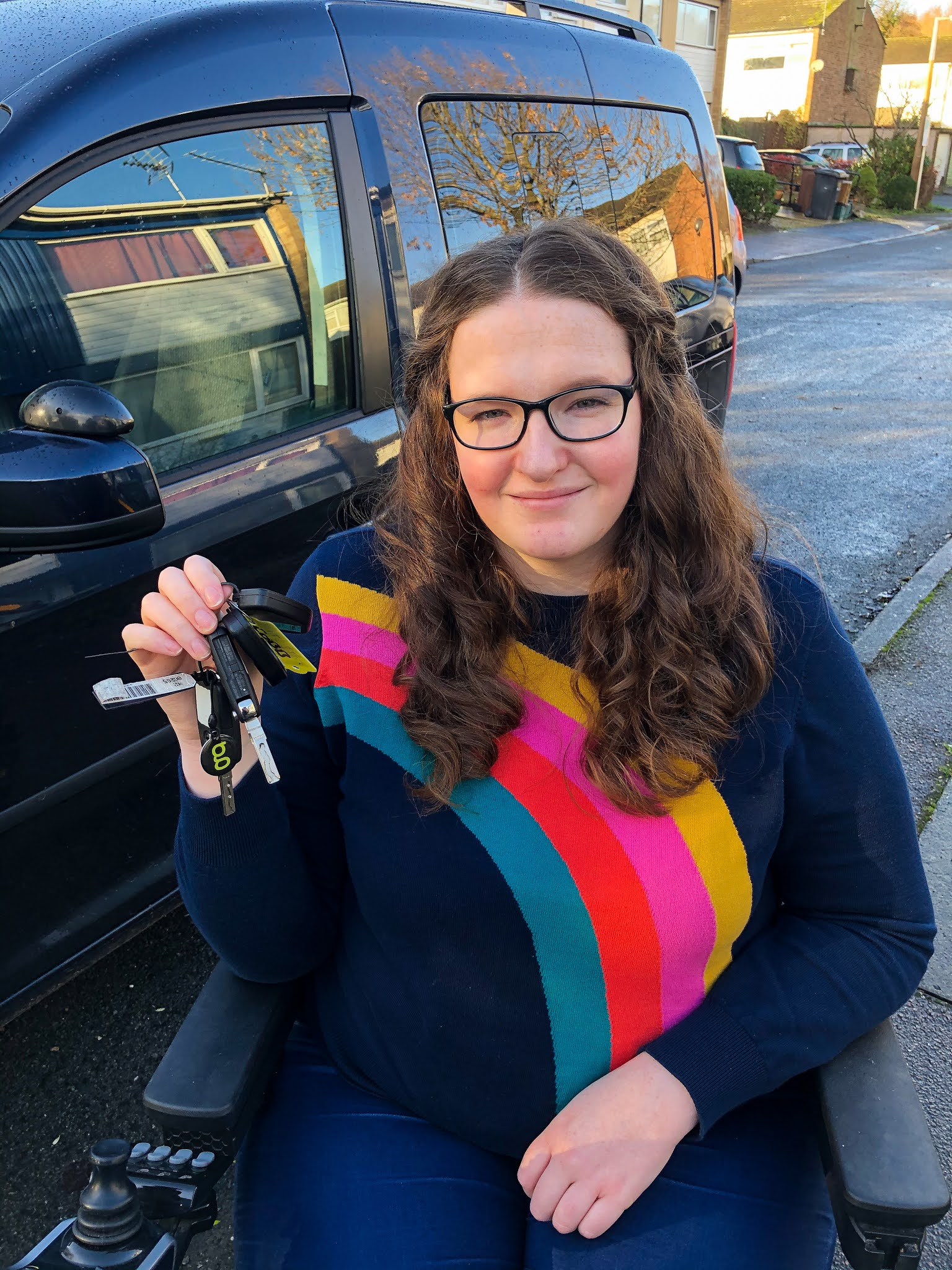 Shona, a young white woman with long curly auburn hair, is sitting in her powerchair in front of her adapted car. She is wearing glasses and a navy jumper with a rainbow on. She is holding up her car keys and smiling.