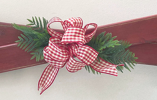 large red and white bow with greenery