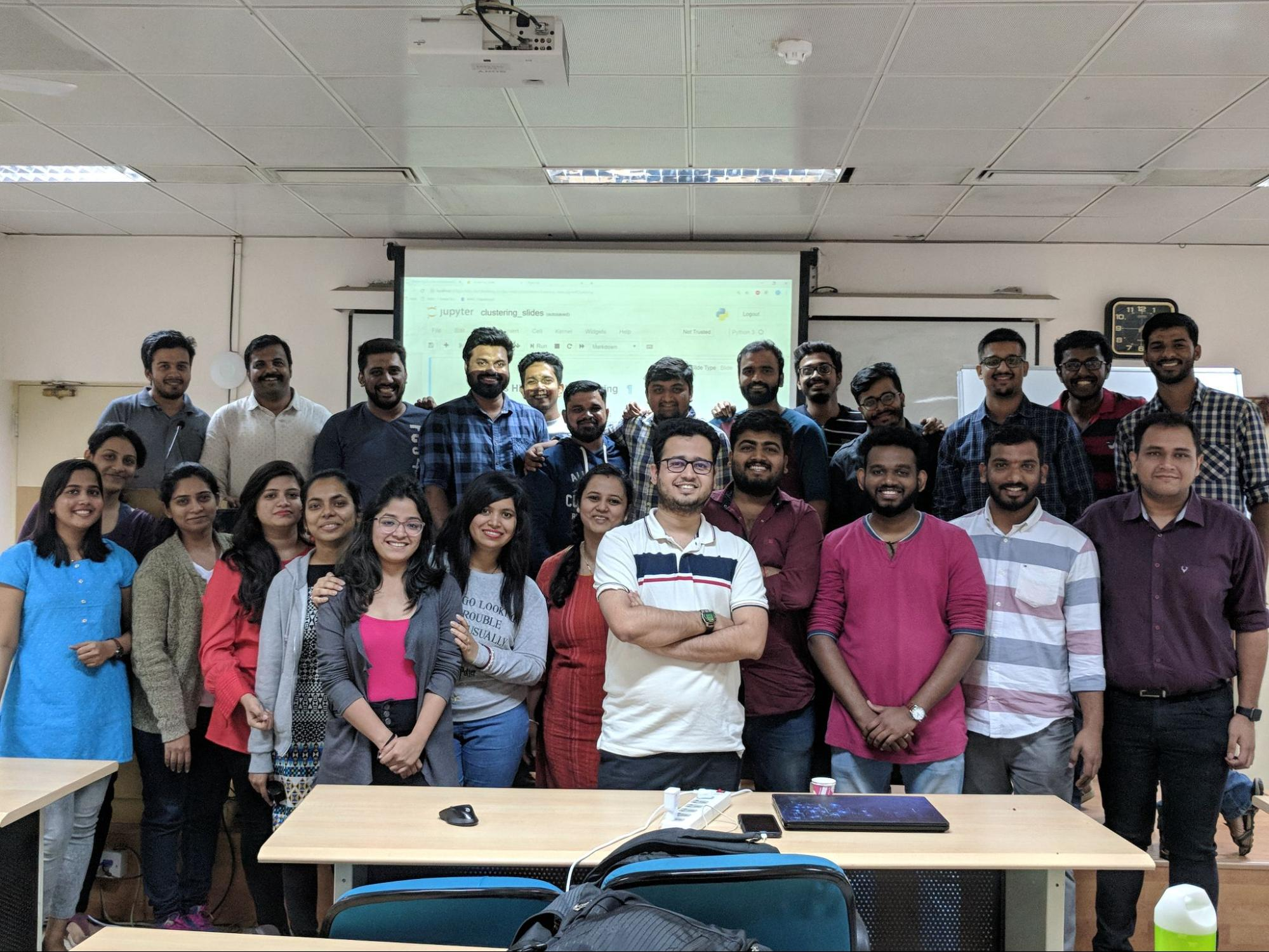 Image shows Bhavesh Bhatt standing in the center of a group of people standing in a classroom and smiling for the camera