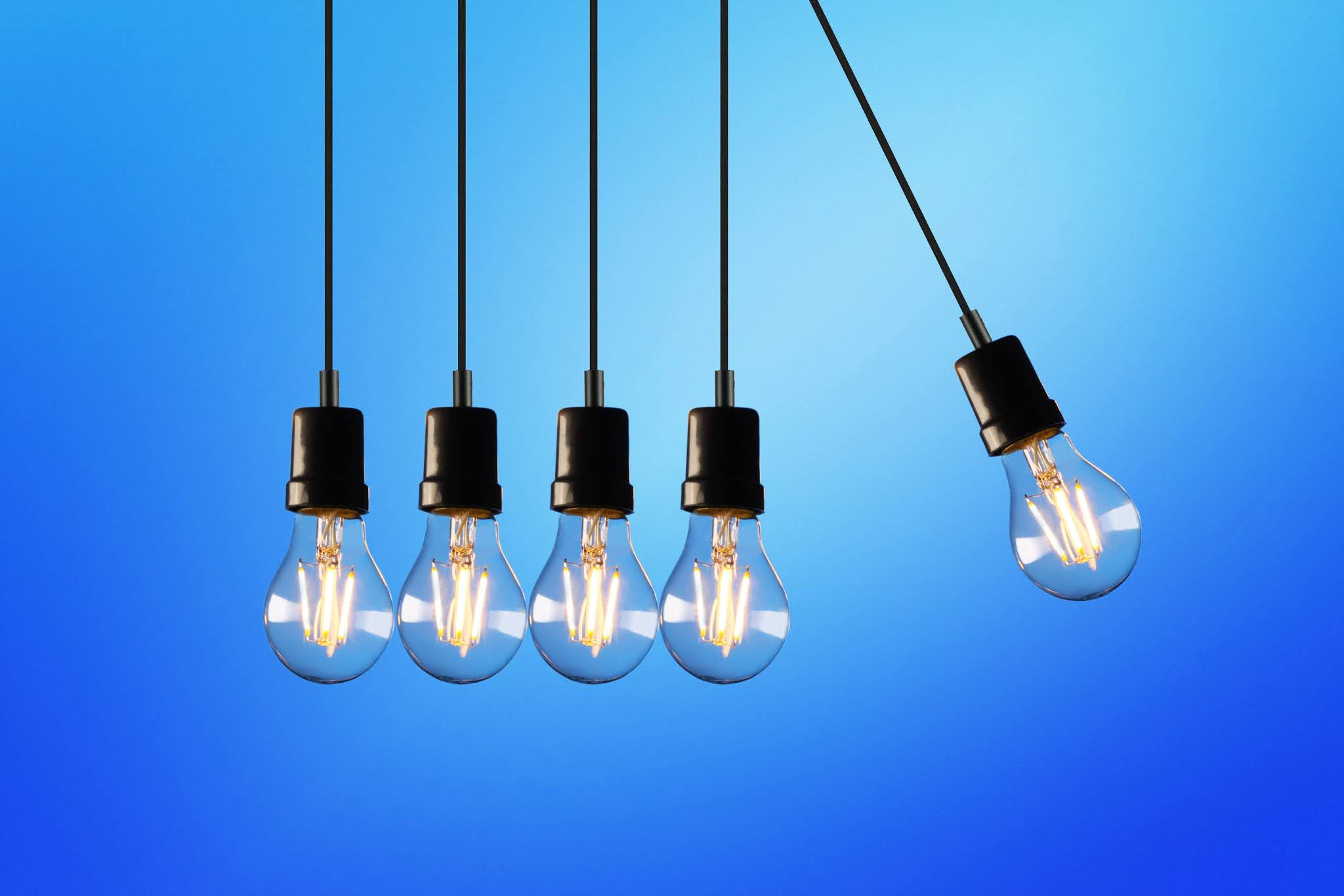 four lightbulbs hanging in a row with one lightbulb swinging to the right away from the line of lightbulbs