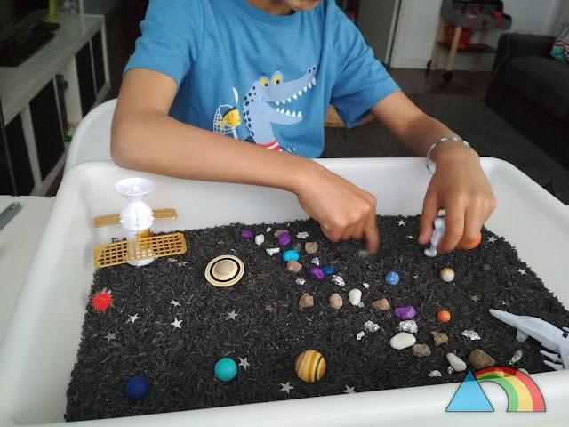 Niño jugando con bandeja sensorial del espacio (arroz teñido de negro, miniaturas de planetas del Sistema Solar, piedras de colores, naves y astronautas de juguete)