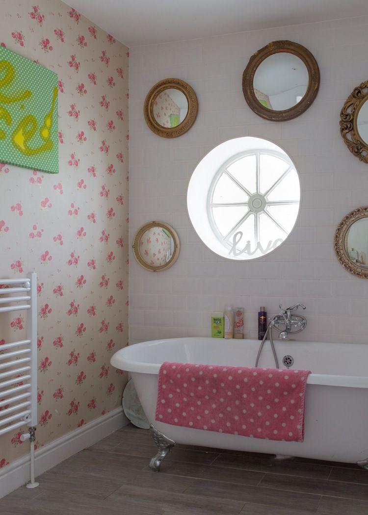 baño con ventana redonda y espejos de igual forma, papel pintado de flores y cuadro tipo graffiti en verde y amarillo