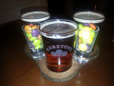 A selection of three glasses of different ales and two shot glasses containing sweets on a wooden stand.