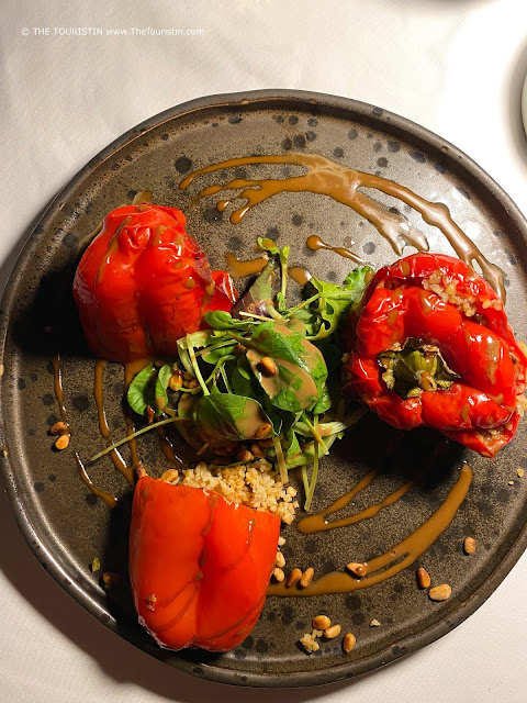 Three stuffed red peppers and spinach salad, sprinkled with pine nuts and sauce served on a grey plate.