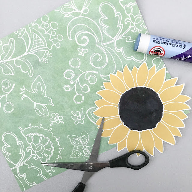 Green craft paper with a white design of flowers and birds, sunflower cut of and a pair of scissors