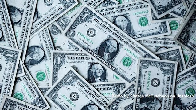 Diversas notas de um dólar jogadas e sobrepostas