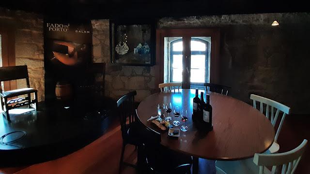 mesa com provas de vinhos do Porto e palco para concerto de fado
