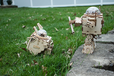 A wooden robot standing on a stone with a stick in one hand and a wooden dog sitting opposite him, on the grass.