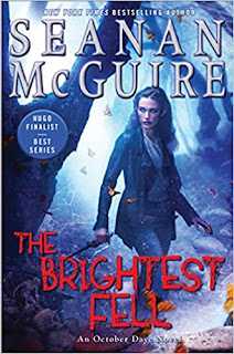 A pale woman with dark hair and pointed ears, wearing a leather jacket and jeans walks through a moonlit forest with a dagger in her hand and a wary look in her eye.