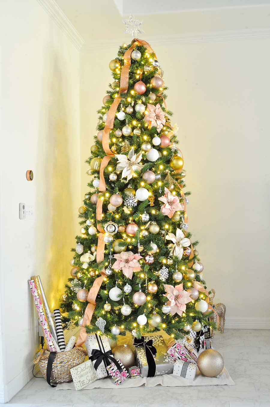 Blush pink Christmas tree decorated with gold, silver, and white ornaments, pink poinsettias and glittery ribbon. What a stunning tree!