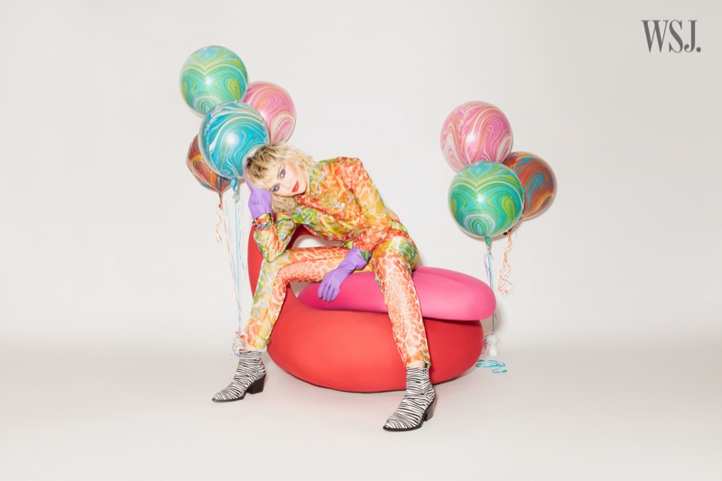 Sporting animal print, Miley Cyrus gets surrounded by balloons.