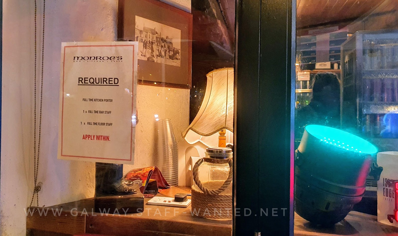 bar window with job advertisement and a large spotlight with a green filter, and an old fashioned table lamp