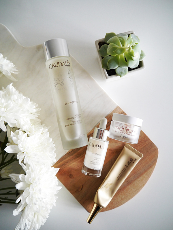 Flat lay featuring Caudalie Vinoperfect Concentrated Brightening Essence and Radiance Serum, Fresh Lotus Youth Preserve moisturizer, The Face Shop eye cream