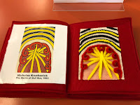 a two page spread with a print of the artwork by Nicholas Krushenick, titled The Battle of Bull Run, 1963, on the left. It is an image with arcs of blue and yellow at the top with an orange, yellow lines crossing each other with red looping shapes in an arc over the lines. On the right is a tactile representation of this image using pipe cleaners in the same colors and patterns