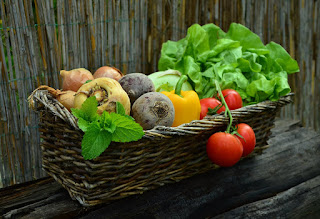 An assortment of fresh vegetables in a greyish-brown basket.