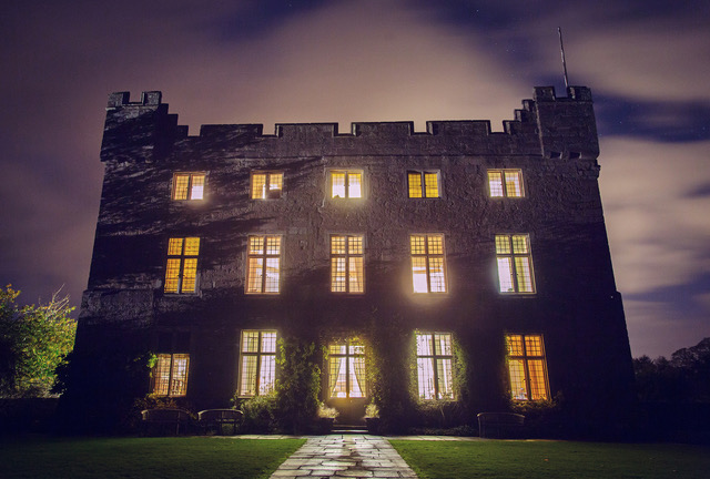 Askham Hall at Night with all the lights on behind large windows