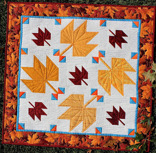 red and yellow maple leaves on a cream background by QuiltFabrication