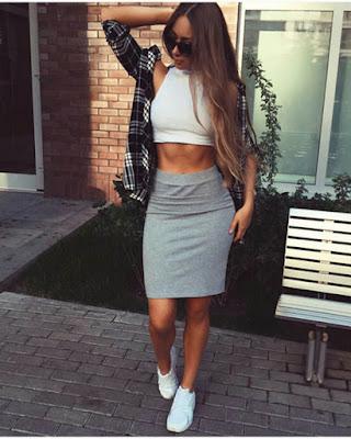 outfit informal de moda con falda lápiz gris y tenis blancos y crop top