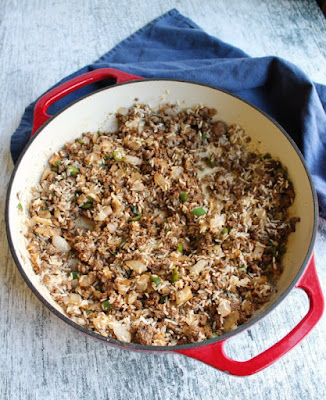 skillet filled with ground beef, taco seasoning, jalapenos, onions and uncooked rice ready for skillet meal