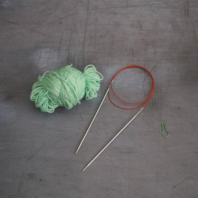 mint yarn, circular needle and green stitch marker