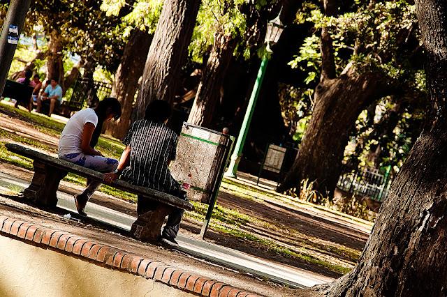 Foto Pareja sentada en silencio en banco de plaza