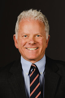 Brad Wiersum smiles in a formal headshot with a black background.