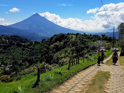 local women walking near Hobbitenango with Agua Volcano in the background