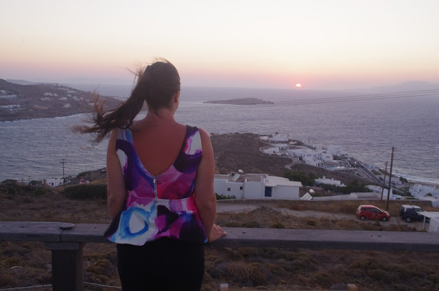 Girl watching sunset on Mykonos Island