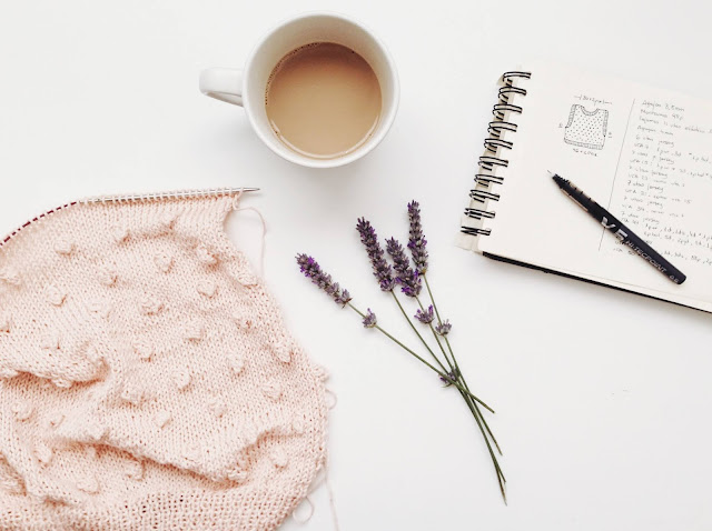 A flatlay with a cup of coffee in the centre. There is a bit of lavender, a knitted scaff and a notebook also in the flatlay
