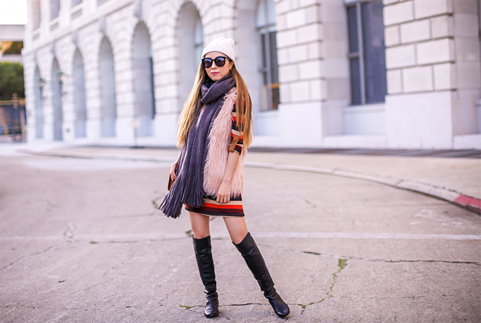 Pink faux fur vest, she in faux fur vest, stripe dress, sezane patti crossbody bag, over the knee boots, stuart weitzman 5050 boots, free people scarf, karen walker super duper sunglasses, j crew pom pom beanie, san francisco fashion blog, san francisco street style, winter style, holiday outfit ideas