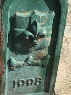the metal base of a street lamp in Lincoln, painted green