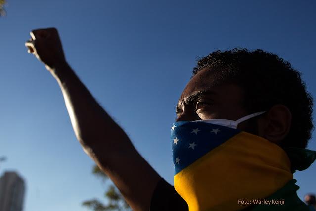 Homem negro usa bandeira do Brasil como máscara e levanta punho fechado como gesto de resistência contra o racismo
