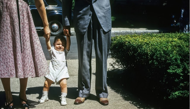 Image: Parents holding the hands of their baby attempting to walk, on VintageStockPhotos
