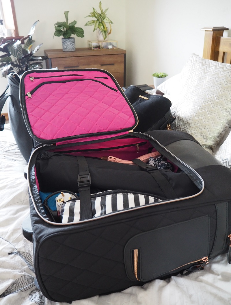 Main compartment of the Travel Hack case packed with clothes, makeup, sunglasses, toiletries, umbrella and tripod