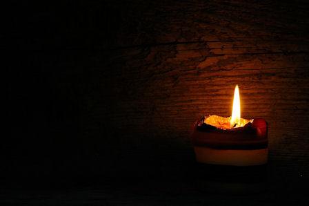 Kynttilän liekki ainoana keskellä rauhallisuutta.