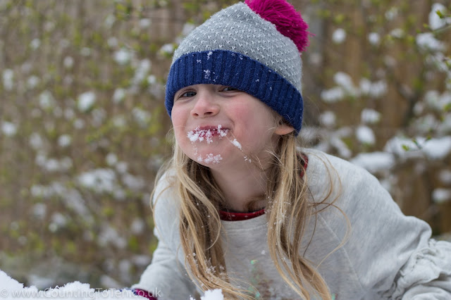 A young girl grinning with snow around her mouth after having eaten some