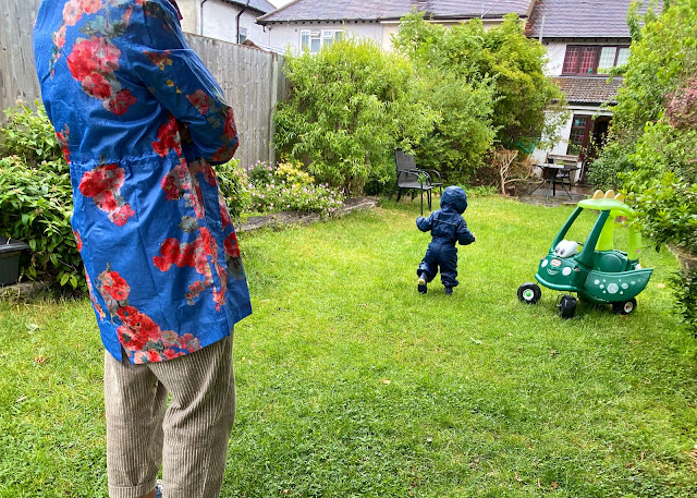 A toddler in a wet garden in a navy puddlesuit at a socially distanced 2 metres from an adult in a waterproof to stay dry from the rain