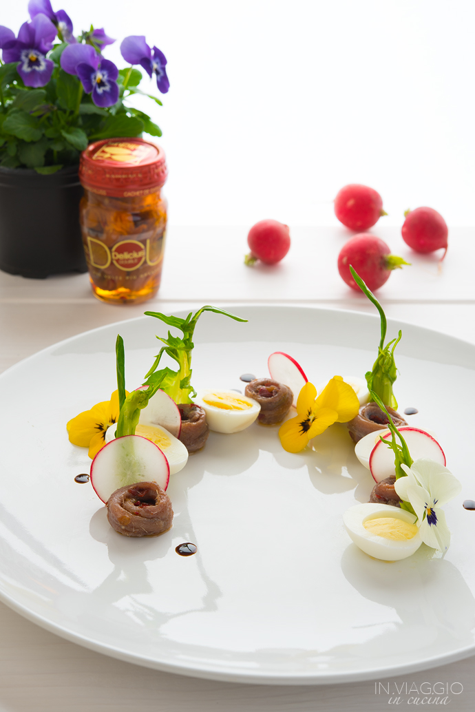 Composed salad with quail eggs, anchovies and edible flowers