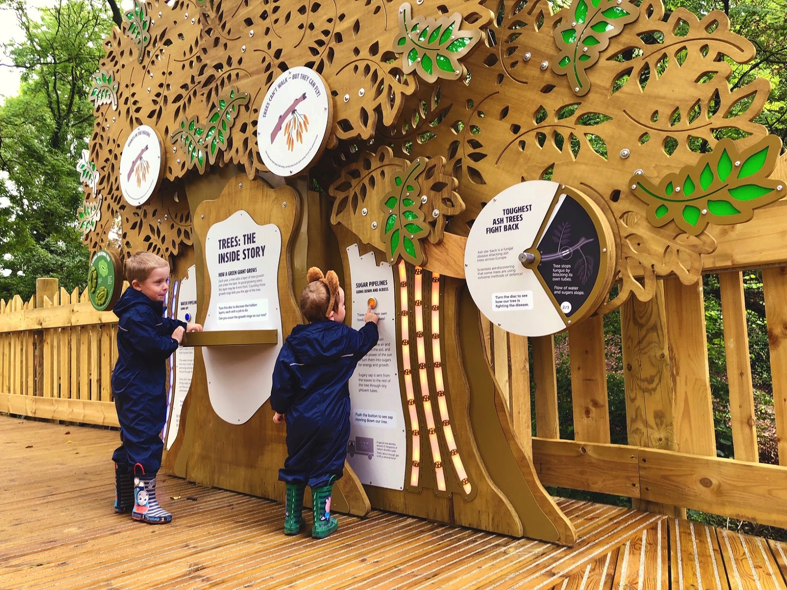 two boys in puddle suits and wellies playing with an interactive game at wild place project