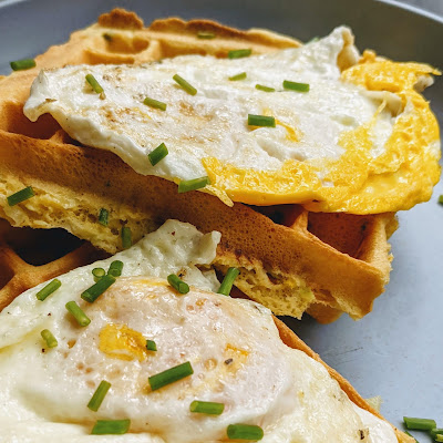 Waffles covered with crispy fried eggs and chives.