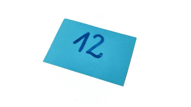 na zdjęciu karteczka w kolorze niebieskim z liczba dwanaście napisane niebieskim markerem