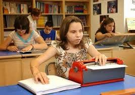 La imagen muestra a una niña leyendo un texto braille y con un una máquina perkins