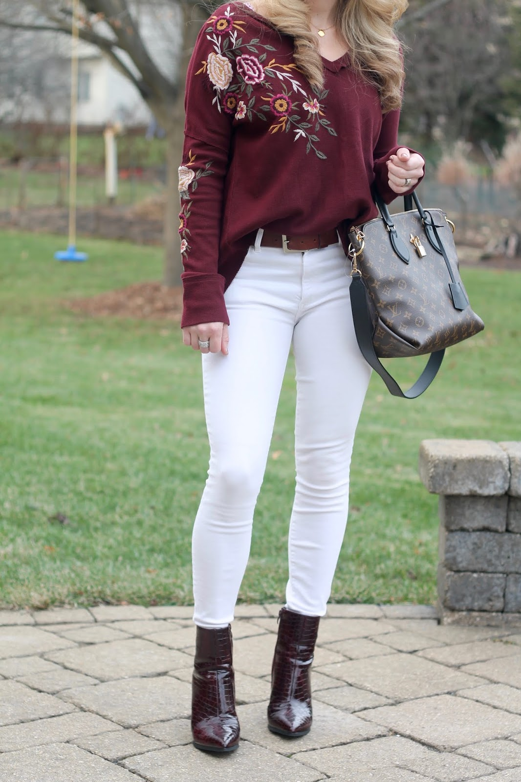 burgundy embroidered top, white jeans, burgundy booties, LV flower zippered tote