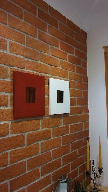 ceglana ściana ozdobiona dwoma lustrami